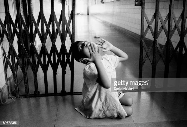 A mentally retarded girl drags herself along a corridor at the Ashasadan Rescue Home for destitute and abandoned children in Manhurst India