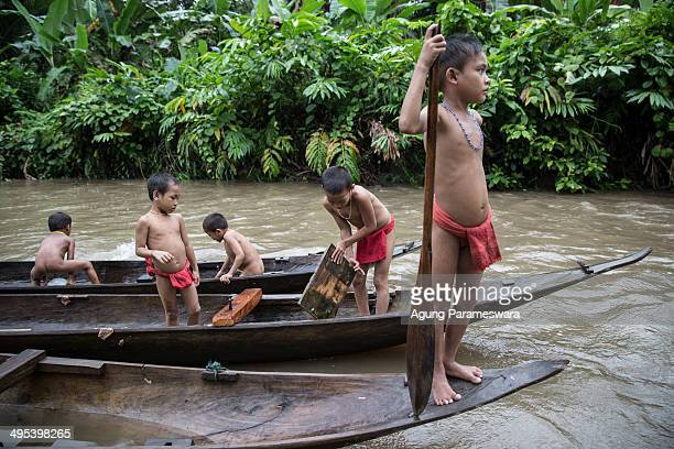 Mentawanese kids play on a traditional canoe on May 26 2014 in Butui Village Siberut Island West Sumatra Indonesia Sikerei is the leader of the...