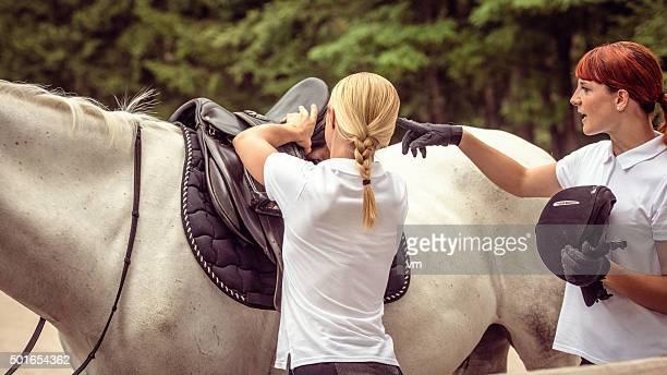 Mentor adjusting horse saddle for her student