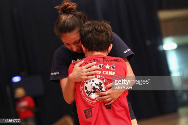 A mentor comforts a child who had an argument with another boy at the TAPS 'Good Grief Camp' on May 26 2012 in Washington DC Five hundred children of...