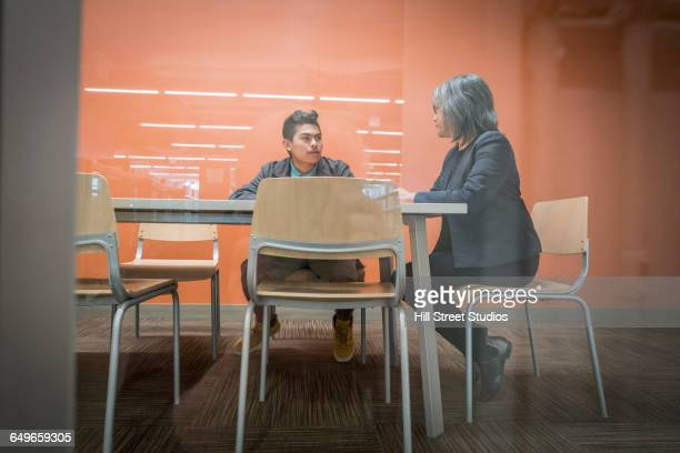 Mentor talking to student in office meeting