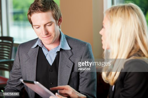 Mentoring: mature woman explaining something to young co-worker