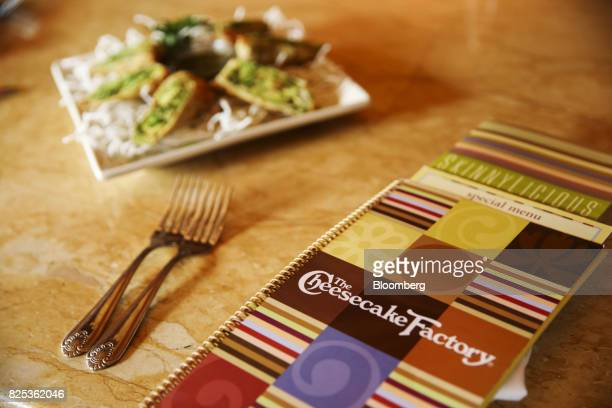 Menus and plate of avocado egg rolls are arranged for a photograph at a Cheesecake Factory Inc restaurant in the Canoga Park neighborhood of Los...