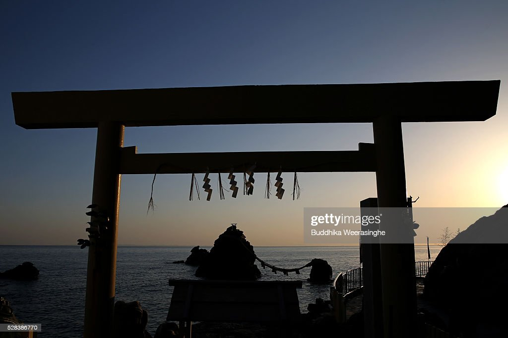'Meoto-Iwa' or couple rocks pictured through the shrine gate as sun rise over the sea ahead of the Oshimenawahari ceremony at Futami Okitama Shrine on May 5, 2016 in Ise, Japan. The Oshimenawahari ceremony is held three times a year to exchange the 35 meters long heavy rope made of rice straw that connects the sacred Couple Rock - one small, one big. The Couple Rock serves as a gate to the Okitama Shrine, dedicated to the god Sarutahiko and goddess Ukanomitama from Japanese myth.