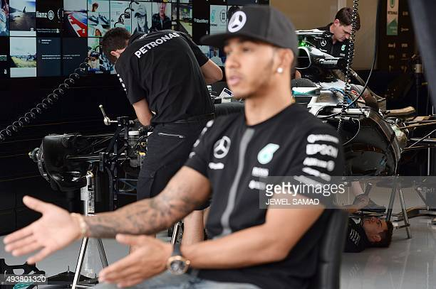 Mercedes AMG Petronas British driver Lewis Hamilton speaks during an interview with a television channel as pit crew work on his car at the pit...