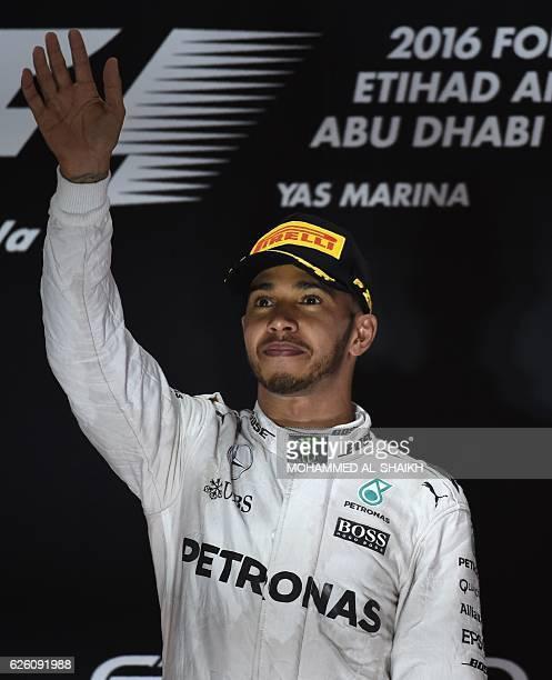 Mercedes AMG Petronas F1 Team's British driver Lewis Hamilton celebrates after winning the Abu Dhabi Formula One Grand Prix at the Yas Marina circuit...