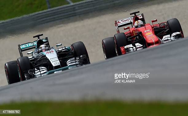 Mercedes AMG Petronas F1 Team's British driver Lewis Hamilton and Ferrari's German driver Sebastian Vettel compete during the qualifying race at the...