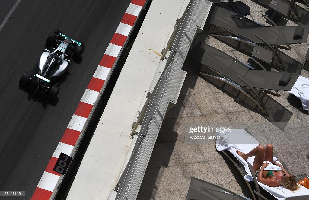 Mercedes AMG Petronas F1 Team's British driver Lewis Hamilton as a woman sunbathes during the second practice session at the Monaco street circuit, on May 26, 2016 in Monaco, three days ahead of the Monaco Formula 1 Grand Prix. / AFP / PASCAL
