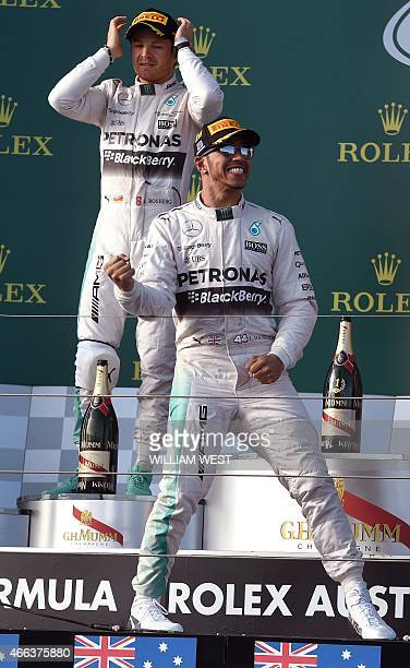 Mercedes AMG Petronas F1 Team's British driver Lewis Hamilton celebrates as teammate German driver Nico Rosberg looks on after winning the Formula...