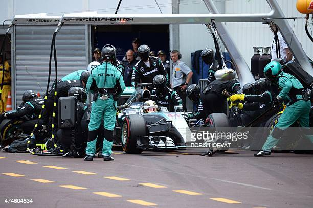 Mercedes AMG Petronas F1 Team's British driver Lewis Hamilton changes his tyres in the pits towards the end of the race at the Monaco street circuit...