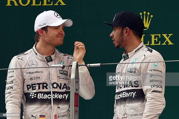 Mercedes AMG Petronas F1 Team's British driver Lewis Hamilton chats with teammate Nico Rosberg of Germany after Hamilton won the Formula One Chinese...