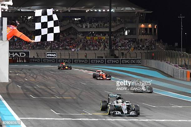 TOPSHOT Mercedes AMG Petronas F1 Team's British driver Lewis Hamilton crosses the finish line at the end of the Abu Dhabi Formula One Grand Prix at...