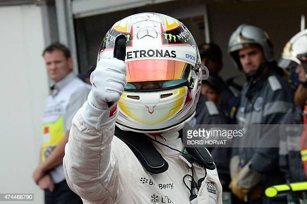 Mercedes AMG Petronas F1 Team's British driver Lewis Hamilton gives the thumbs up as he celebrates taking the pole position in the pits after after...