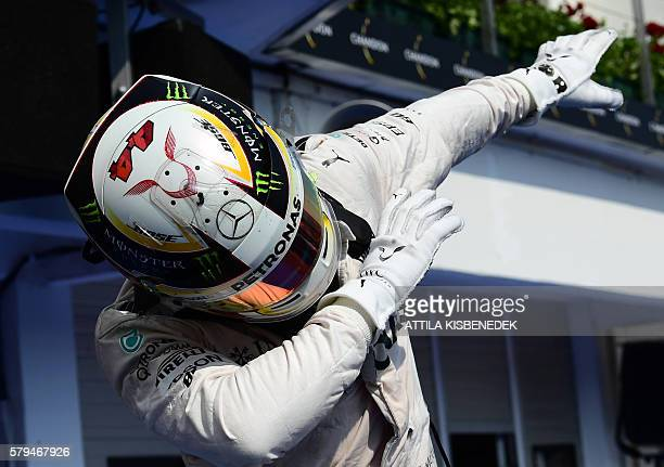 Mercedes AMG Petronas F1 Team's British driver Lewis Hamilton celebrates his victory at the Hungaroring circuit in Budapest on July 24 2016 after the...
