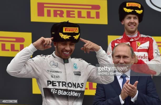 Mercedes AMG Petronas F1 Team's British driver Lewis Hamilton celebrates his victory on the podium as Russian President Vladimir Putin and second...