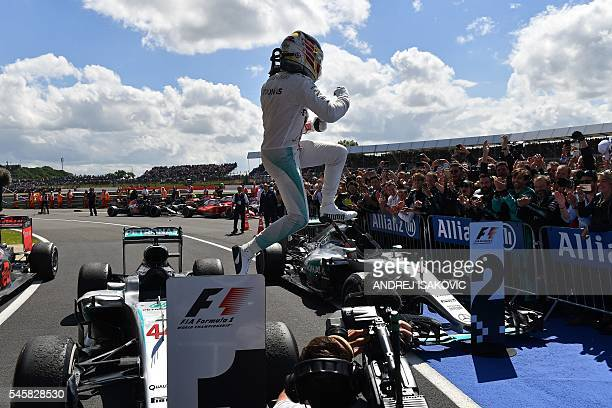 TOPSHOT Mercedes AMG Petronas F1 Team's British driver Lewis Hamilton jumps from his car after winning the British Formula One Grand Prix at...