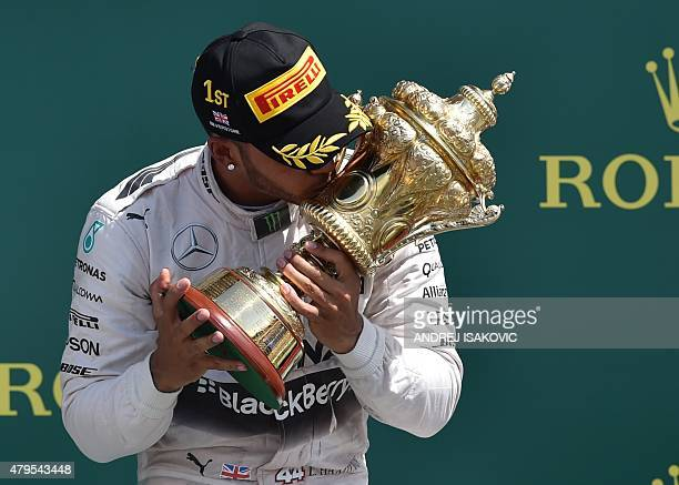 Mercedes AMG Petronas F1 Team's British driver Lewis Hamilton kisses the trophy on the podium after winning the British Formula One Grand Prix at the...