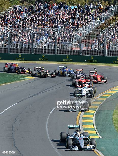 Mercedes AMG Petronas F1 Team's British driver Lewis Hamilton leads the pack around the first corner during the Formula One Australian Grand Prix in...
