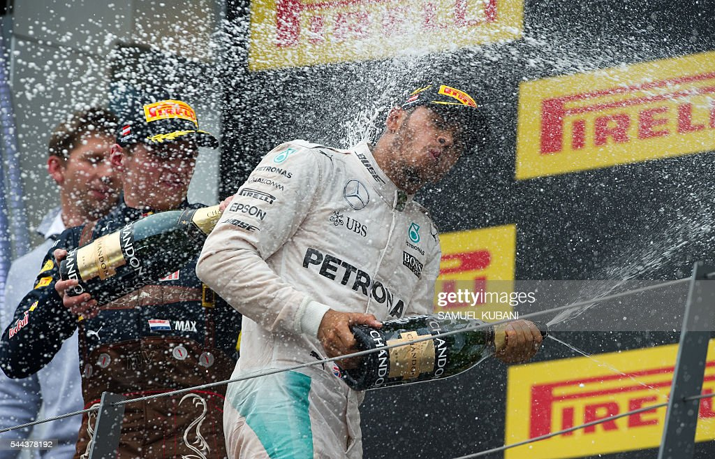 Mercedes AMG Petronas F1 Team's British driver Lewis Hamilton celebrates on podium with Infiniti Red Bull racing's BelgianDutch driver Max Verstappen...