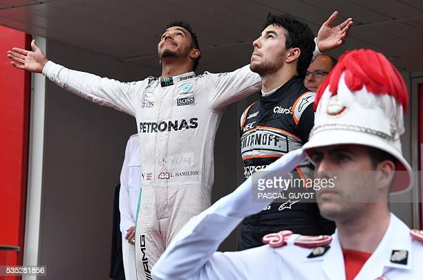 Mercedes AMG Petronas F1 Team's British driver Lewis Hamilton celebrates on the podium as he wins next to Sahara Force India F1 Team's Mexican driver...