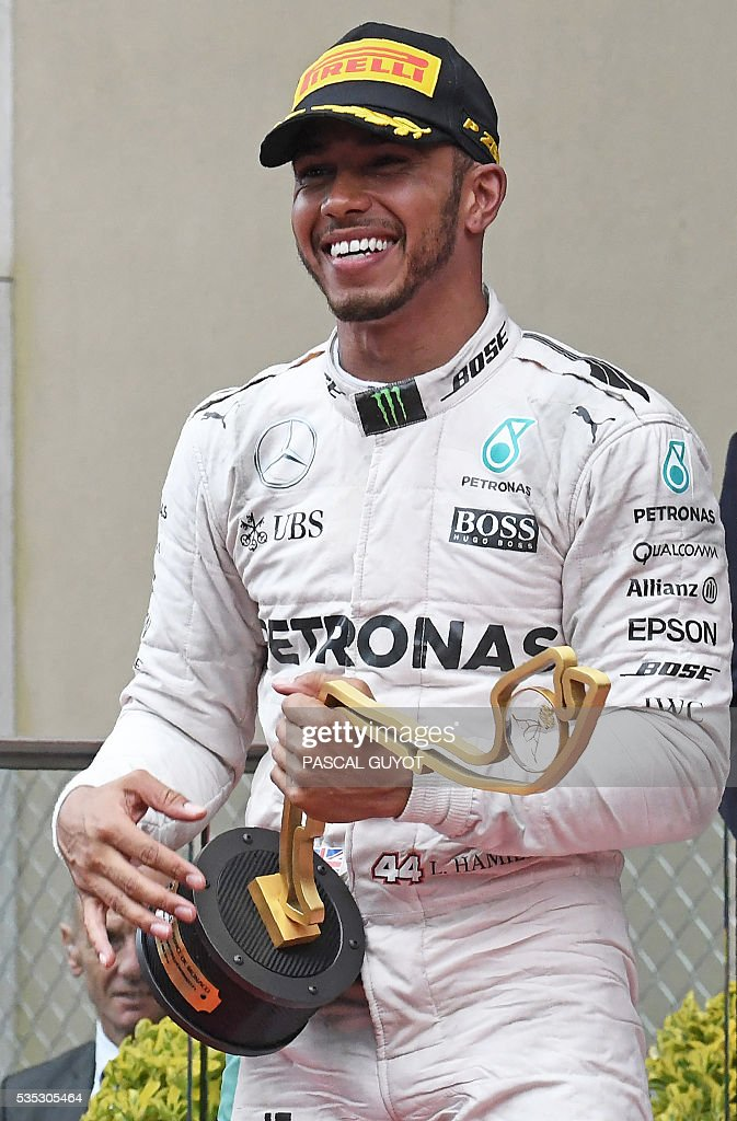 Mercedes AMG Petronas F1 Team's British driver Lewis Hamilton celebrates on the podium with his trophy the Monaco street circuit, on May 29, 2016 in Monaco, after the Monaco Formula 1 Grand Prix. / AFP / PASCAL