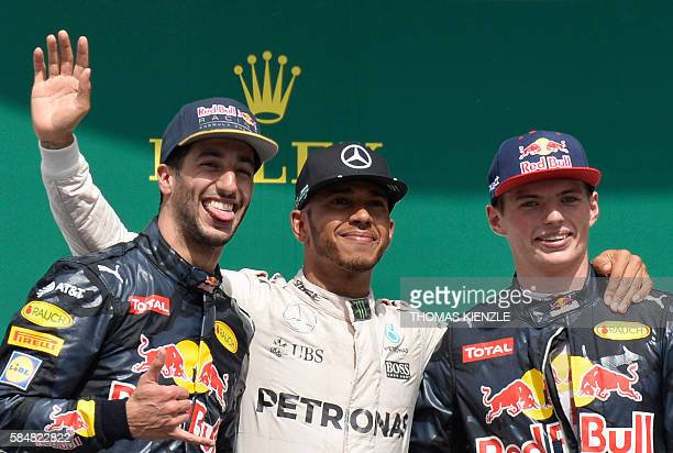 TOPSHOT Mercedes AMG Petronas F1 Team's British driver Lewis Hamilton poses during the winner ceremony on the podium after winning next to second...