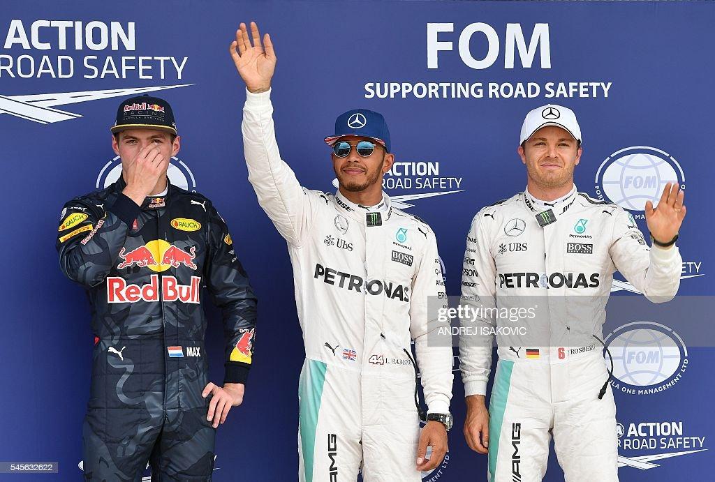 Mercedes AMG Petronas F1 Team's British driver Lewis Hamilton stands alongside Mercedes AMG Petronas F1 Team's German driver Nico Rosberg and...