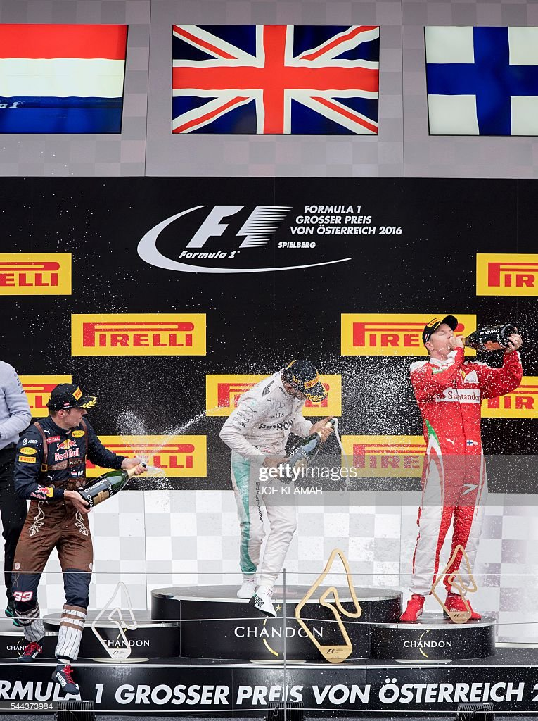 Mercedes AMG Petronas F1 Team's British driver Lewis Hamilton celebrates victory on the podium ahead of Infiniti Red Bull racing's BelgianDutch...
