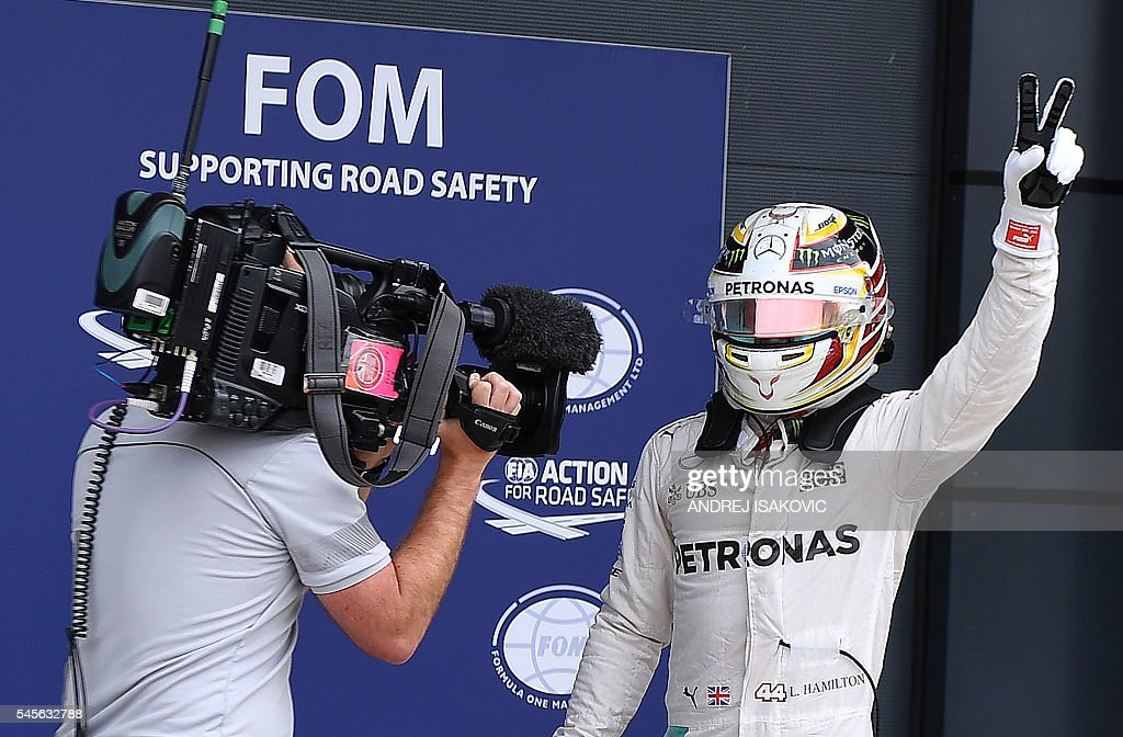 Mercedes AMG Petronas F1 Team's British driver Lewis Hamilton waves to the fans after taking pole position in tomorrow's British Formula One Grand...