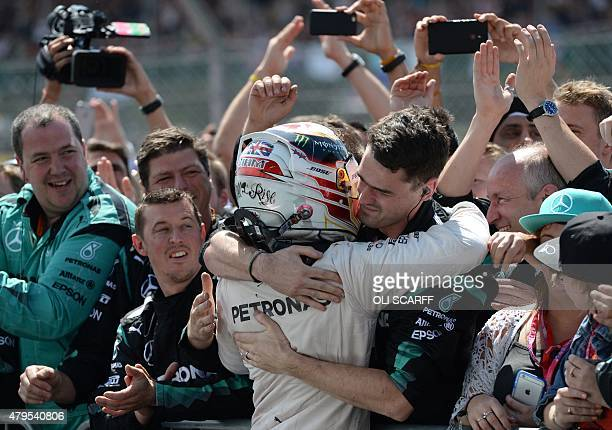 Mercedes AMG Petronas F1 Team's British driver Lewis Hamilton celebrates with teammates after winning the British Formula One Grand Prix at the...