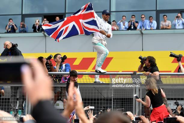 TOPSHOT Mercedes AMG Petronas F1 Team's British driver Lewis Hamilton celebrates with fans after climbing the paddock fence after winning the British...