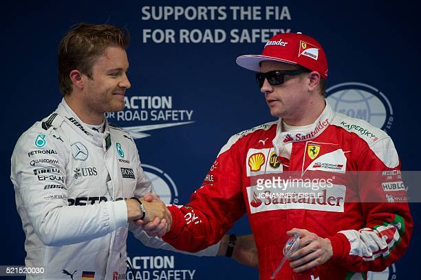 Mercedes AMG Petronas F1 Team's German driver Nico Rosberg and Ferrari's Finnish driver Kimi Raikkonen shake hands after qualifying at the Formula...