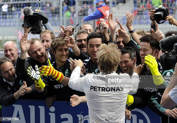 Mercedes AMG Petronas F1 Team's German driver Nico Rosberg celebrates with members of his team after winning the Austrian Formula One Grand Prix at...