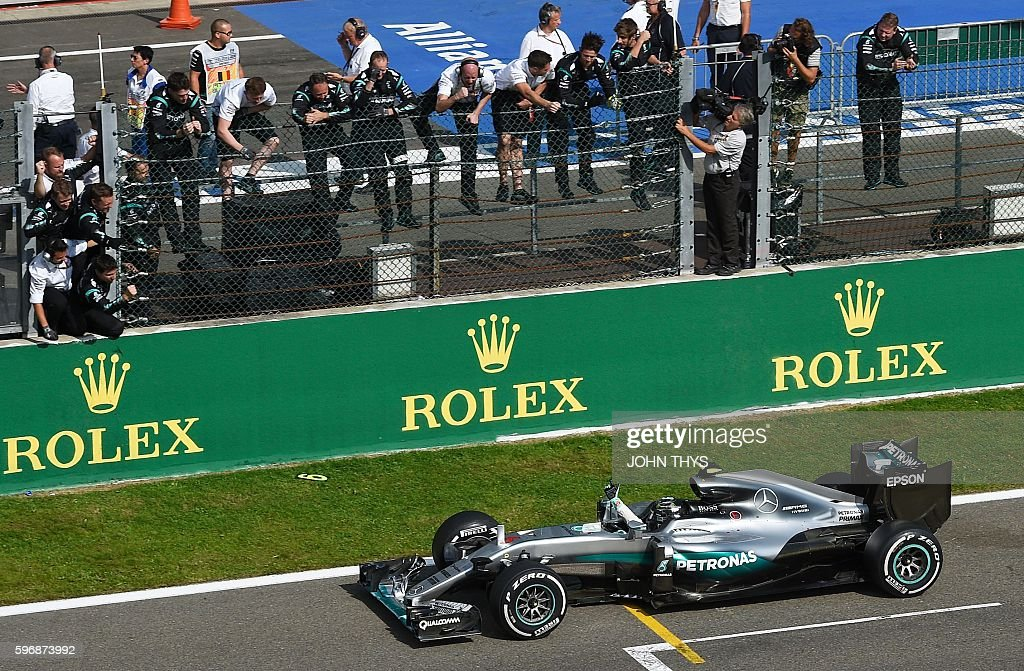 Mercedes AMG Petronas F1 Team's German driver Nico Rosberg celebrates with team members after winning the Belgian Formula One Grand Prix at the...