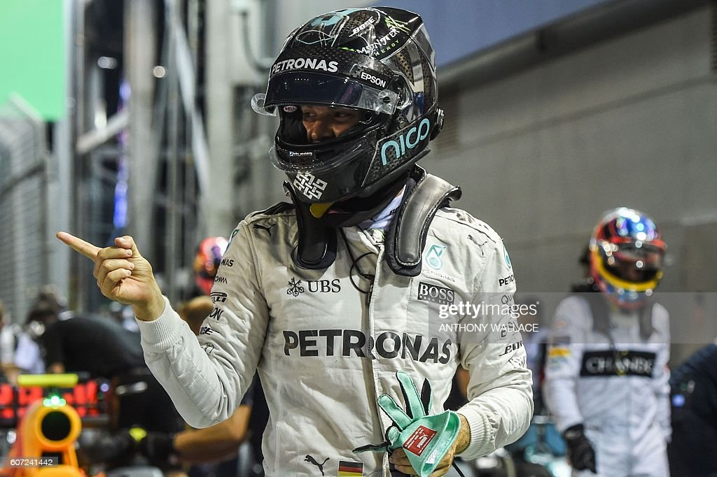 Mercedes AMG Petronas F1 Team's German driver Nico Rosberg celebrates pole position as he arrives in the pit after the qualifying session on September 17, 2016, ahead of the Formula One Grand Prix night race. / AFP / Anthony WALLACE