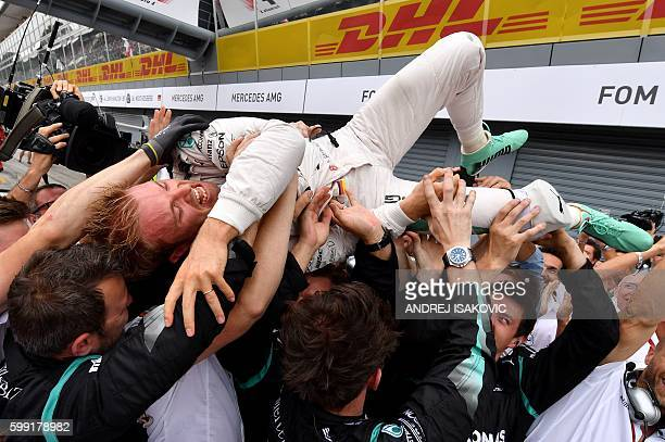Mercedes AMG Petronas F1 Team's German driver Nico Rosberg cheers with his team after winning the Italian Formula One Grand Prix at the Autodromo...