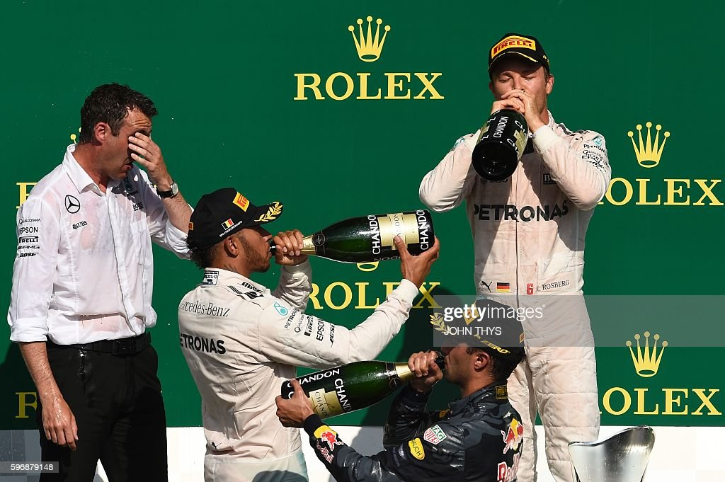Mercedes AMG Petronas F1 Team's German driver Nico Rosberg drinks champagne as he celebrates winning next to second placed Red Bull Racing's...