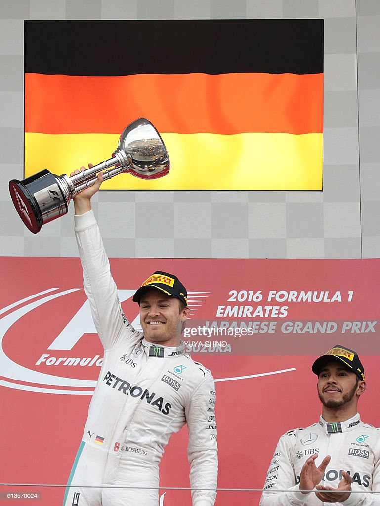 Mercedes AMG Petronas F1 Team's German driver Nico Rosberg (L) holding his trophy celebrates his victory on the podium next to his teammate and third-placed Mercedes AMG Petronas F1 Team's British driver Lewis Hamilton after the Formula One Japanese Grand Prix at the Suzuka Circuit on October 9, 2016. / AFP / YUYA