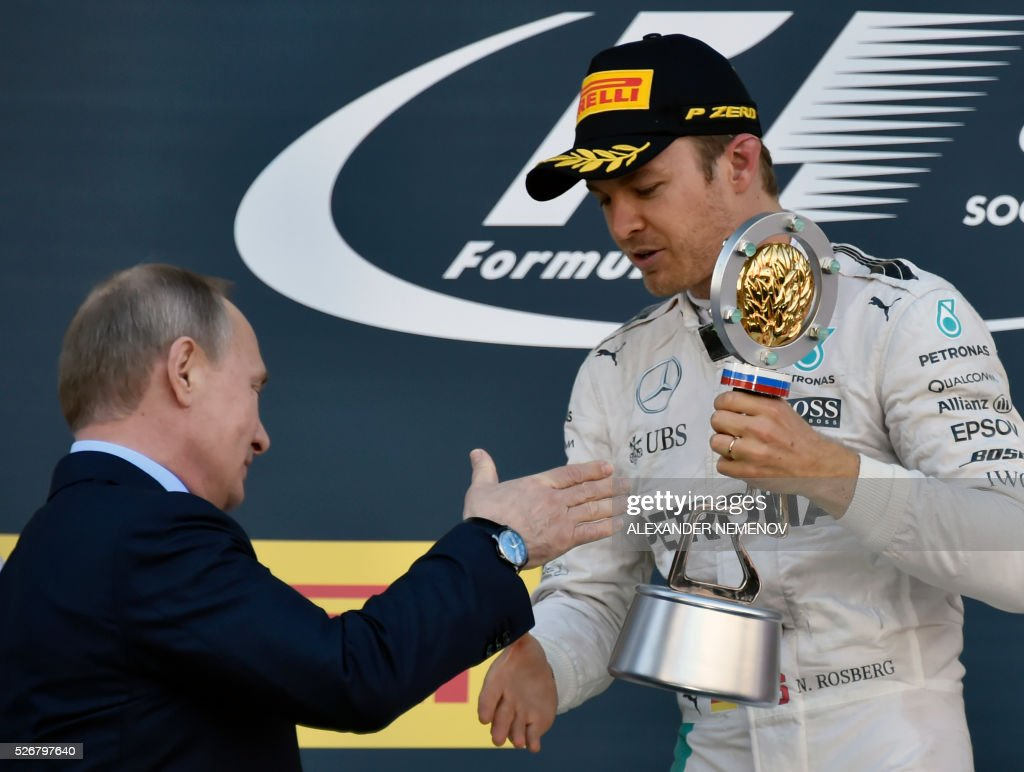 Mercedes AMG Petronas F1 Team's German driver Nico Rosberg is congratulated by Russian President Vladimir Putin after winning the Formula One Russian Grand Prix at the Sochi Autodrom circuit on May 1, 2016. / AFP / ALEXANDER