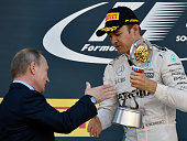 Mercedes AMG Petronas F1 Team's German driver Nico Rosberg is congratulated by Russian President Vladimir Putin after winning the Formula One Russian...