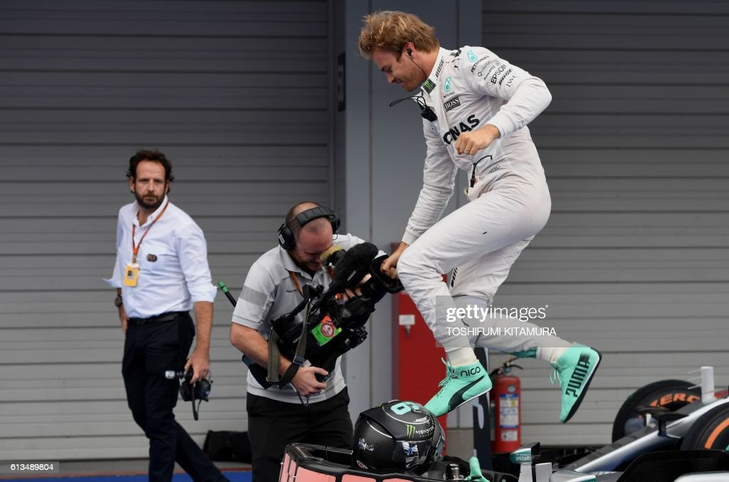 TOPSHOT - Mercedes AMG Petronas F1 Team's German driver Nico Rosberg jumps from his car, after winning the Formula One Japanese Grand Prix race in Suzuka on October 9, 2016. / AFP PHOTO / TOSHIFUMI KITAMURA / The erroneous mention[s] appearing in the metadata of this photo by TOSHIFUMI KITAMURA has been modified in AFP systems in the following manner: [October 9] instead of [October 7]. Please immediately remove the erroneous mention[s] from all your online services and delete it (them) from your servers. If you have been authorized by AFP to distribute it (them) to third parties, please ensure that the same actions are carried out by them. Failure to promptly comply with these instructions will entail liability on your part for any continued or post notification usage. Therefore we thank you very much for all your attention and prompt action. We are sorry for the inconvenience this notification may cause and remain at your disposal for any further information you may require.