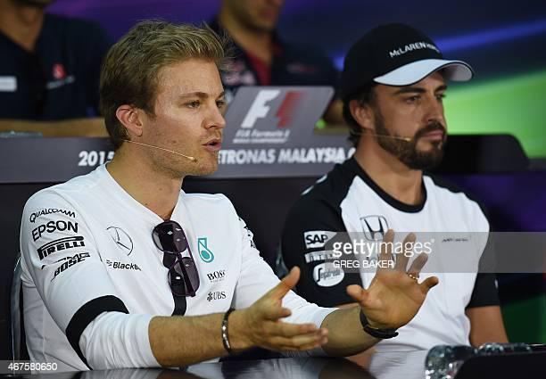 Mercedes AMG Petronas F1 Team's German driver Nico Rosberg speaks as McLaren Honda's Spanish driver Fernando Alonso listens during a press conference...