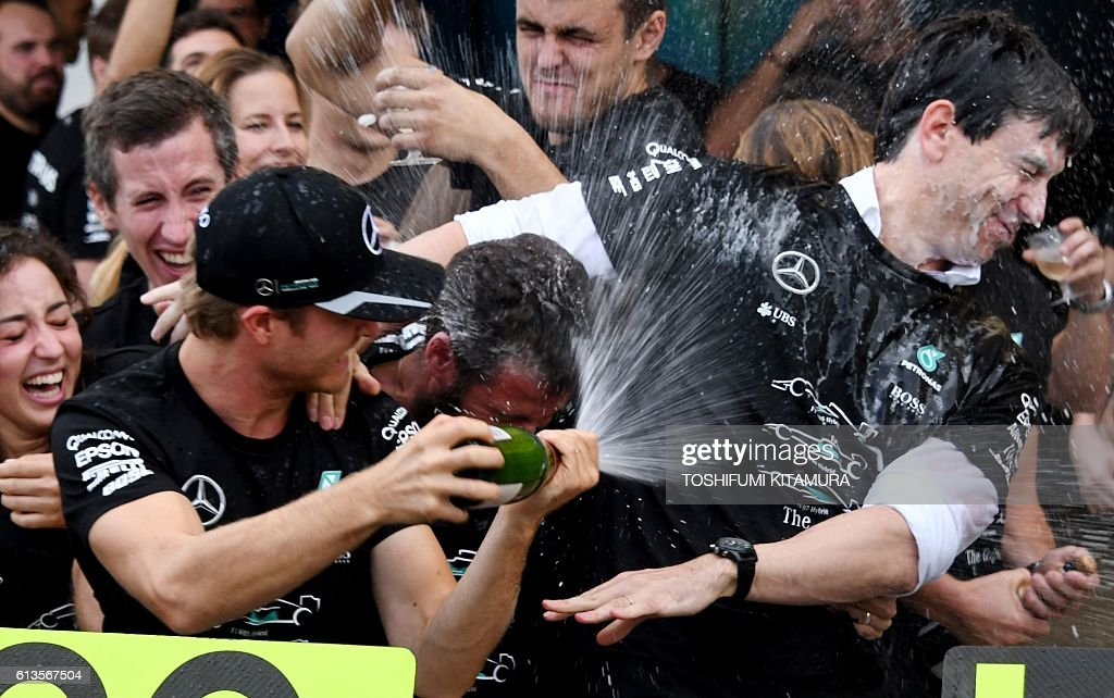 Mercedes AMG Petronas F1 Team's German driver Nico Rosberg (front 2nd L) sprays champagne at the team's managing director Toto Wolff (R) during the team's constructor champion celebration at the Formula One Japanese Grand Prix in Suzuka on October 9, 2016. / AFP / TOSHIFUMI