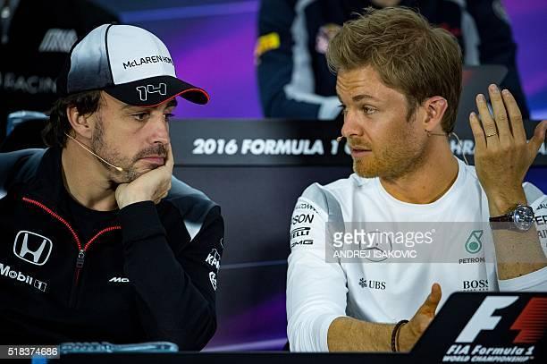 Mercedes AMG Petronas F1 Team's German driver Nico Rosberg talks to McLaren Honda's Spanish driver Fernando Alonso during the drivers press...