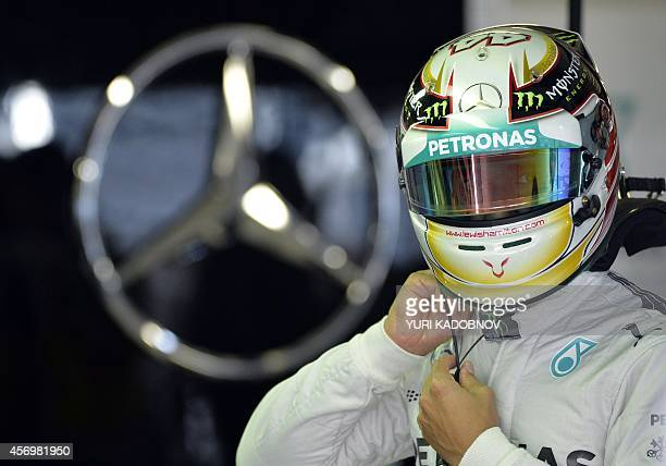 Mercedes' British driver Lewis Hamilton adjusts his helmet during the second free practice session of the inaugural Russian Grand Prix at the Sochi...