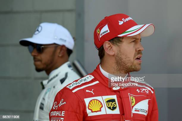 Mercedes' British driver Lewis Hamilton and Ferrari's German driver Sebastian Vettel stand in the parc ferme after the qualifying session at the...