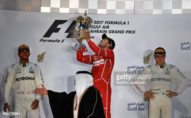 Mercedes' British driver Lewis Hamilton and Mercedes' Finnish driver Valtteri Bottas stand on the podium as Ferrari's German driver Sebastian Vettel...