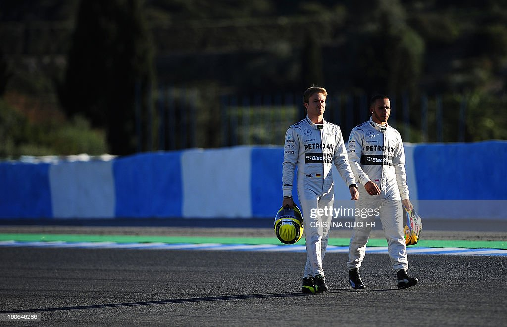Mercedes' British driver Lewis Hamilton (R) and Mercedes' German driver Nico Rosberg arrive to pose during a training session at the Jerez de la Frontera racetrack on February 4, 2013.