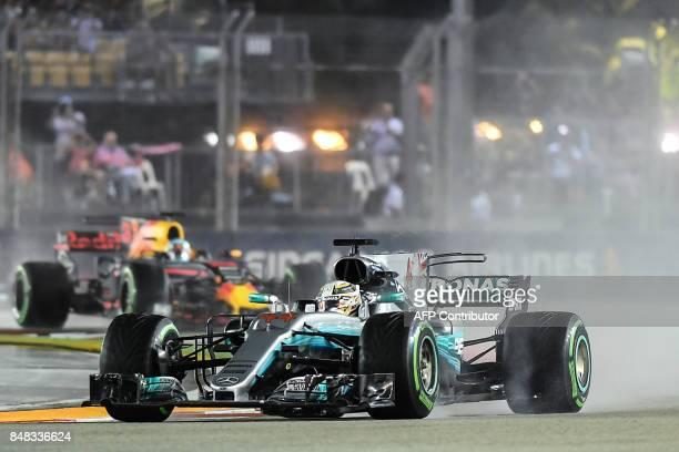 Mercedes' British driver Lewis Hamilton and Red Bull's Australian driver Daniel Ricciardo compete during the Formula One Singapore Grand Prix in...
