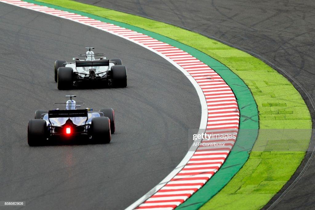 Mercedes' British driver Lewis Hamilton (top) and Sauber's Swedish driver Marcus Ericsson drive during the qualifying session of the Formula One Japanese Grand Prix at Suzuka on October 7, 2017. / AFP PHOTO / Kiyoshi OTA